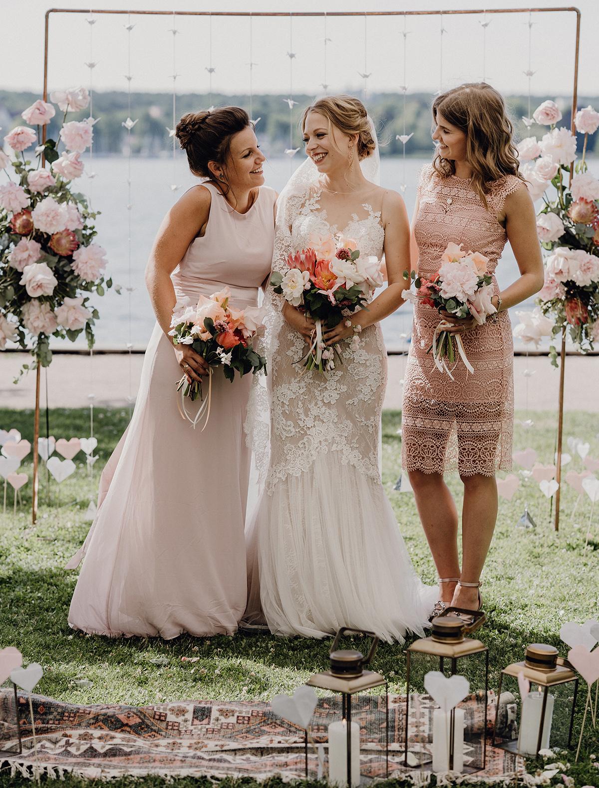 Hochzeitsfotografie Braut mit Brautjungfern vor Traubogen bei Boho Hochzeit - Villa Blumenfisch Berlin Hochzeitsfotograf © www.hochzeitslicht.de