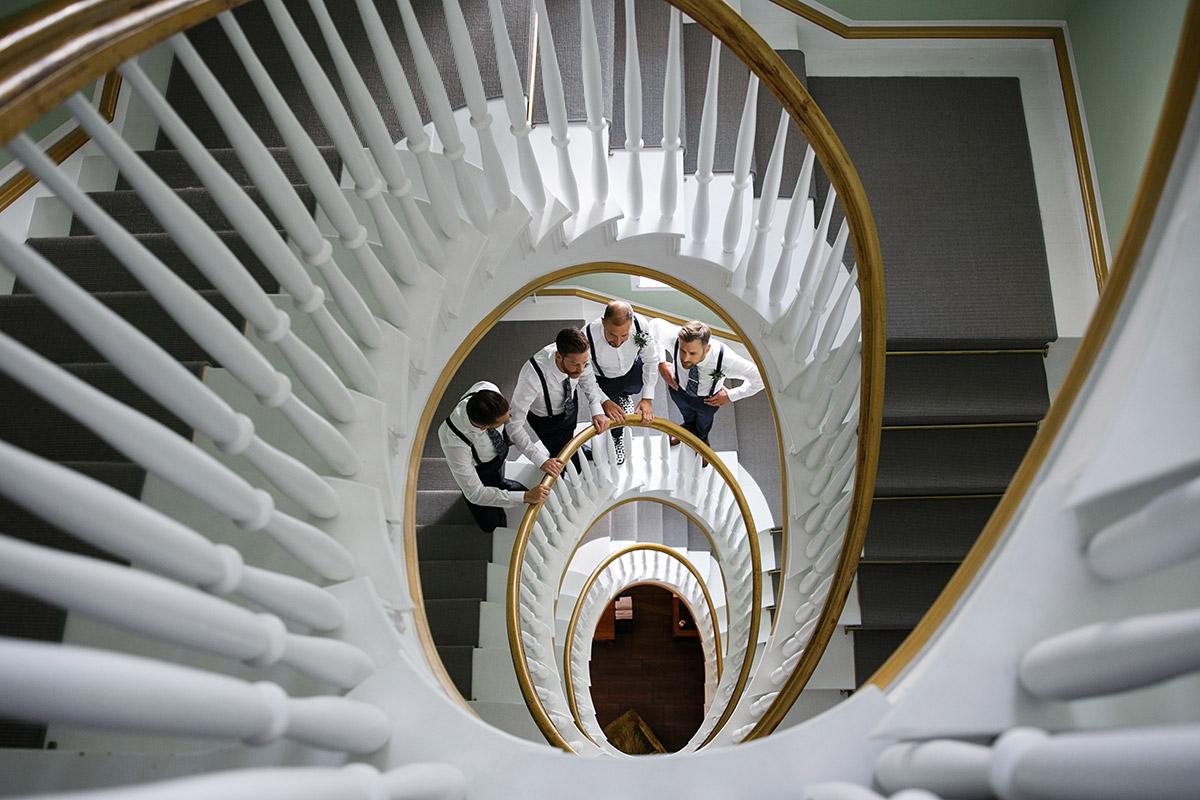 Bräutigam mit Best Men in schönem Spiraltreppenhaus - Sage Restaurant Berlin Hochzeitsfotograf © www.hochzeitslicht.de