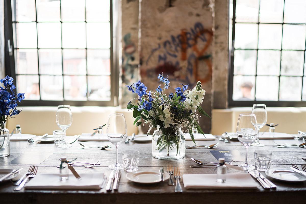 sommerlich-urbane Tischdekoration mit blauen und weißen Blumen - Sage Restaurant Berlin Hochzeitsfotograf © www.hochzeitslicht.de