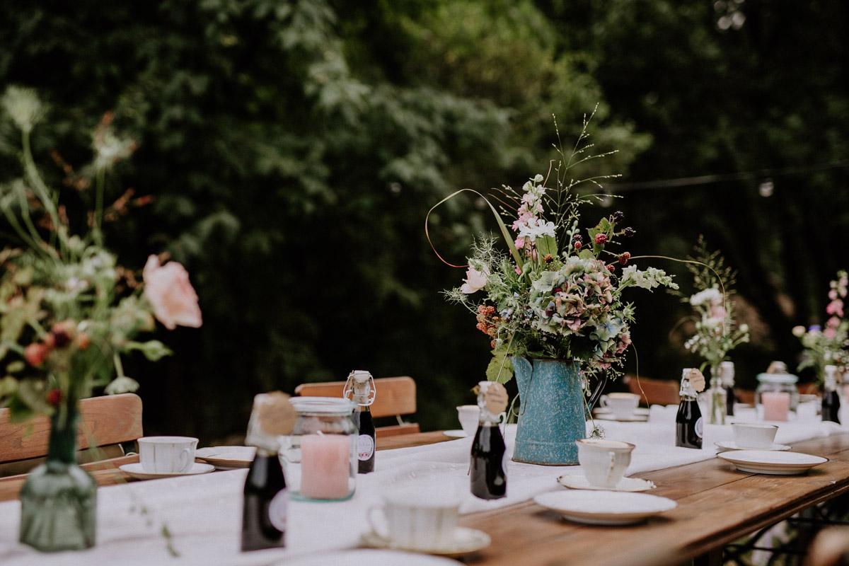 Hochzeitsfoto natürliche Tischdekoration mit Sommer-Blumen, emaillierten Kannen, rosa Kerzen in Weckgläsern bei Hochzeit Museumsdorf Düppel - Hochzeitsvilla Zehlendorf Berlin Hochzeitsfotograf © www.hochzeitslicht.de
