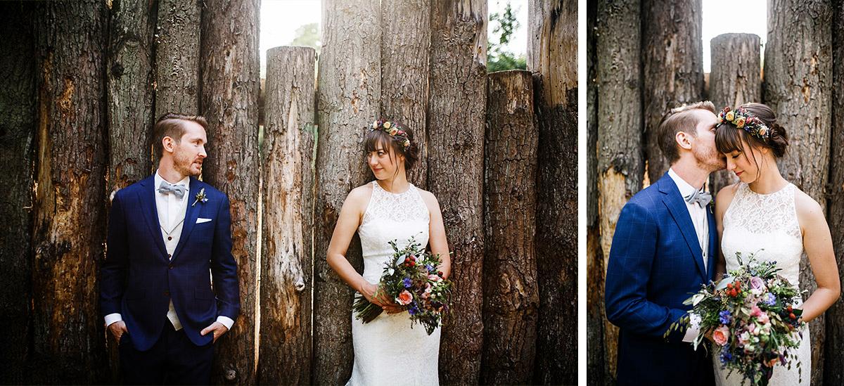 modernes Hochzeitsfoto von Brautpaar vor Holzstämmen bei Sommerhochzeit - Hochzeitsvilla Zehlendorf Berlin Hochzeitsfotograf © www.hochzeitslicht.de