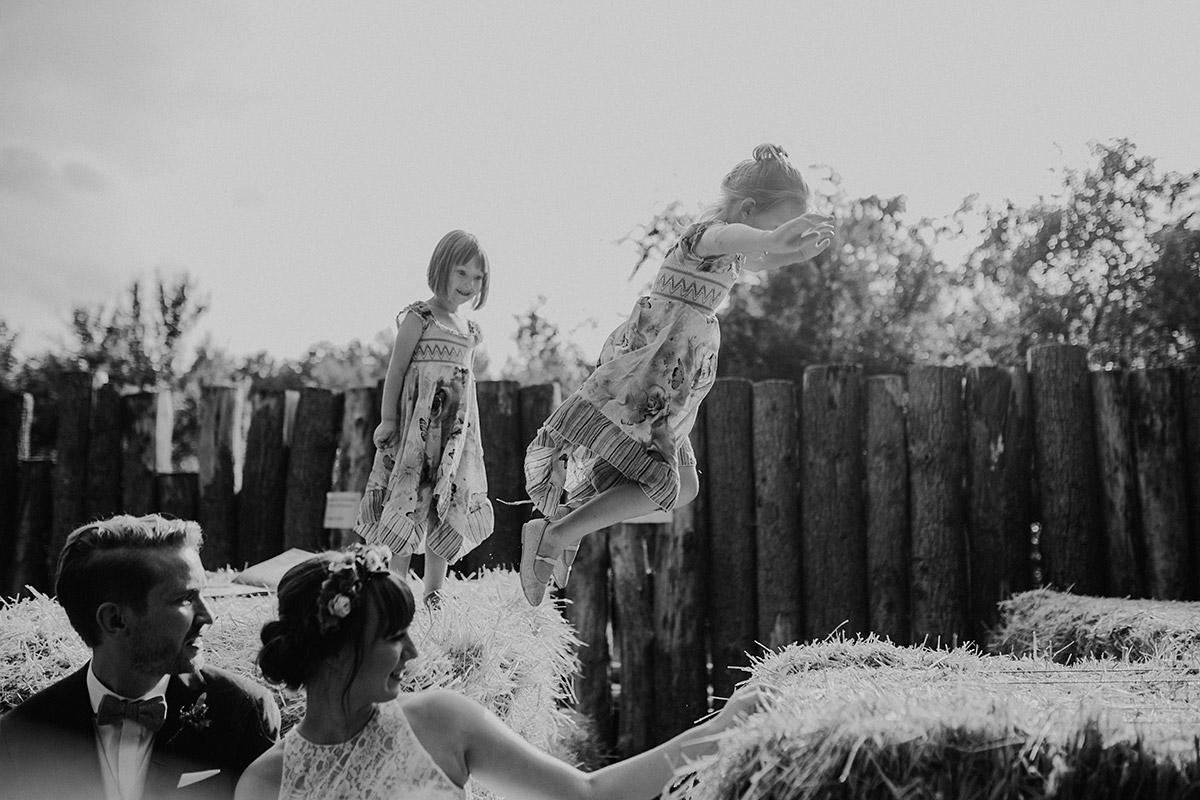 Kinder hüpfen über Heuballen bei Brautpaarfotoshooting im Museumsdorf Düppel - Hochzeitsvilla Zehlendorf Berlin Hochzeitsfotograf © www.hochzeitslicht.de