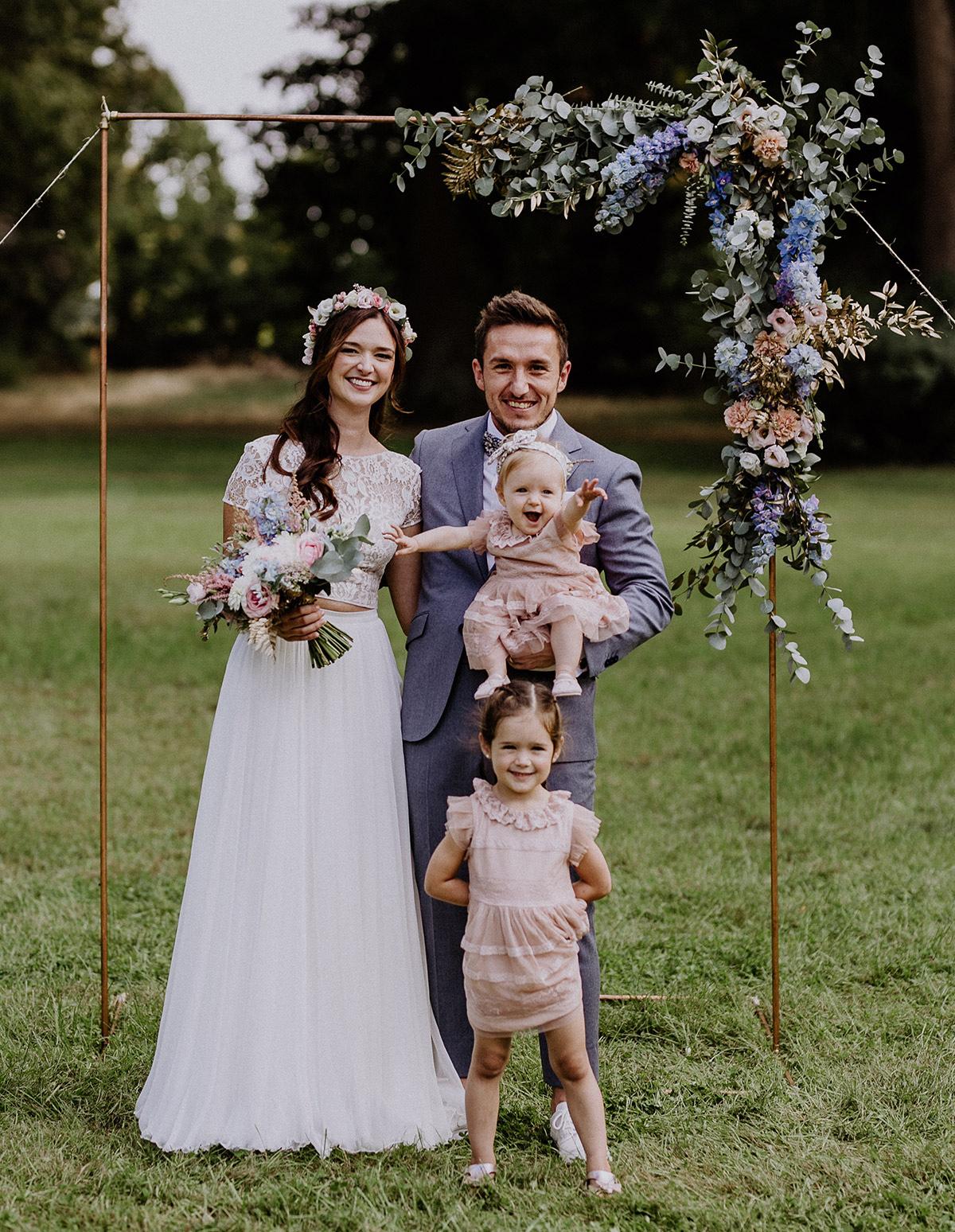 Familienfoto Brautpaar mit Kindern vor Traubogen aus Kupferrohr mit Blumenschmuck, Eukalyptus und Farn - Schloss Kartzow Potsdam Hochzeitsfotograf © www.hochzeitslicht.de