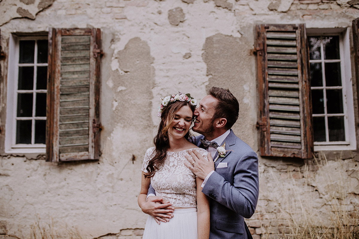 fröhliches Hochzeitsfoto Brautpaar vor alter Fassade - Schloss Kartzow Potsdam Hochzeitsfotograf © www.hochzeitslicht.de