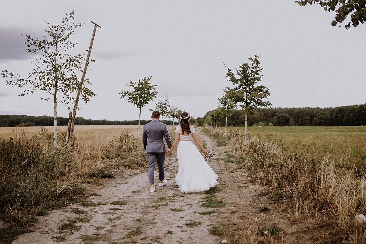 ungestellte Hochzeitsfotografie von Brautpaar bei Sommerhochzeit an Feld - Schloss Kartzow Potsdam Hochzeitsfotograf © www.hochzeitslicht.de