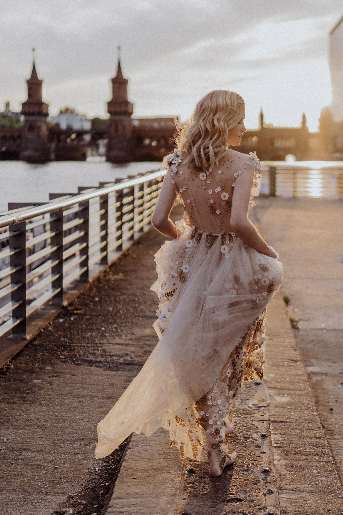 Braut barfuß in mit Blumen besticktem Brautkleid am Spreeufer an der Oberbaumbrücke bei Sonnenuntergang - Berlin Hochzeitsfotograf © www.hochzeitslicht.de