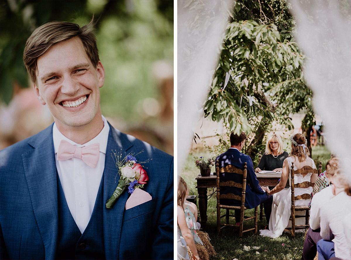 strahlender Bräutigam in blauem Anzug mit rosa Fliege und rosa Einstecktuch - Vierseithofcafé Brandenburg Hochzeitsfotograf © www.hochzeitslicht.de