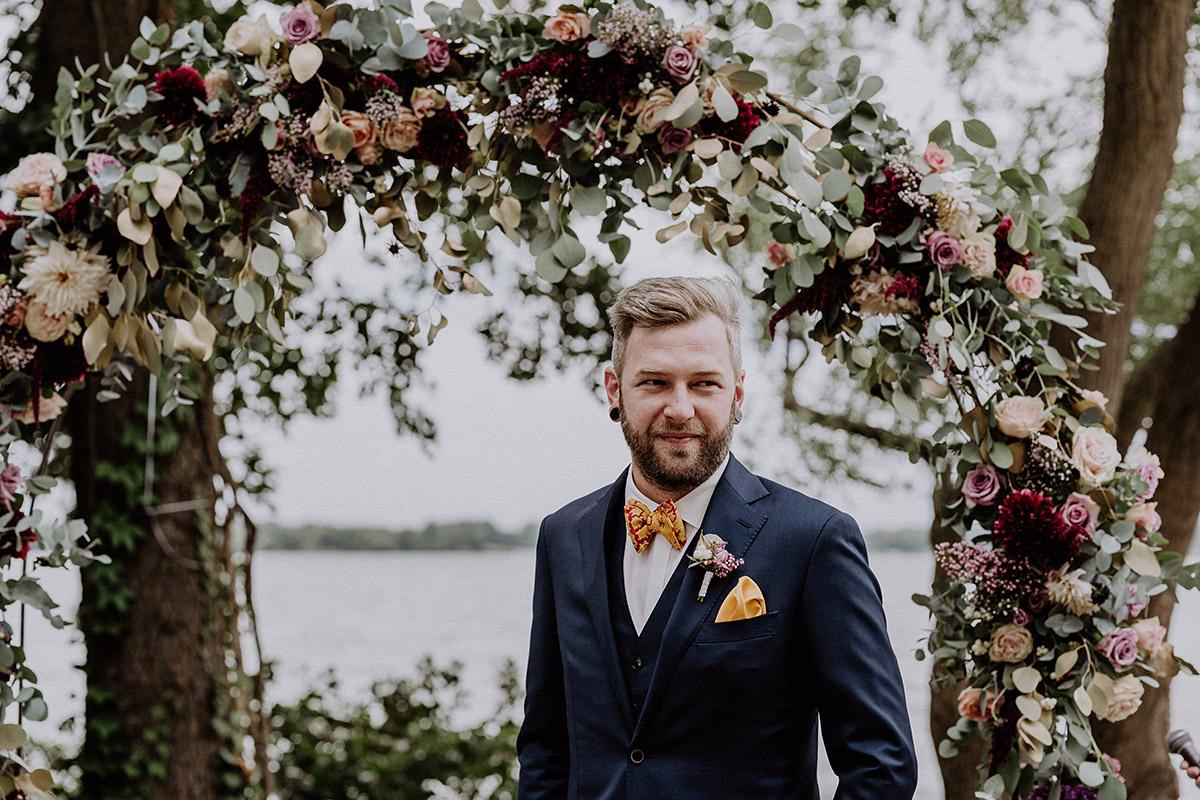 ungestelltes Hochzeitsfoto von Bräutigam vor Blumenbogen freie Trauung am See - Gut Schloss Golm Potsdam Hochzeitsfotograf © www.hochzeitslicht.de