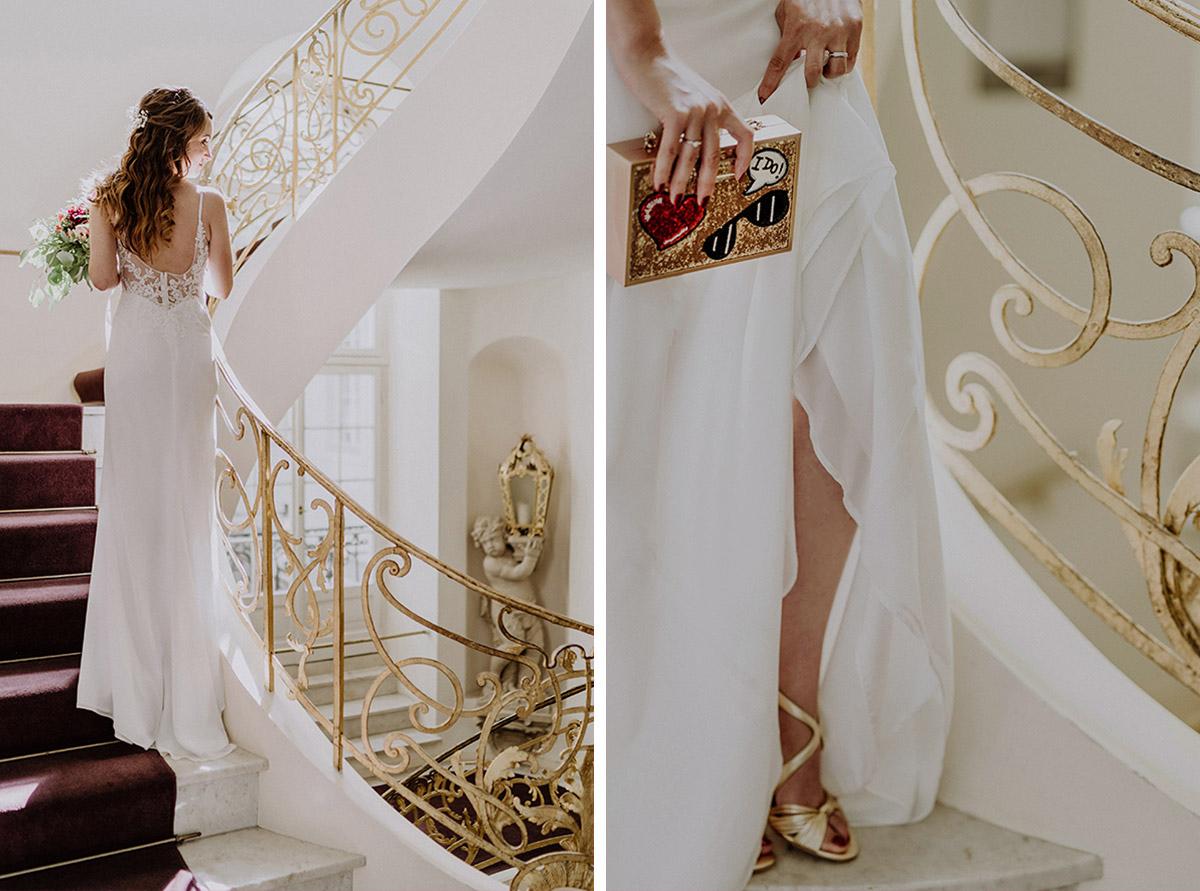 Hochzeitsfoto von Braut im Treppenhaus Ermelerhaus mit rückenfreiem Brautkleid, goldenen Brautschuhen und goldener Glitterclutch - Ermelerhaus Berlin Hochzeitsfotograf © www.hochzeitslicht.de