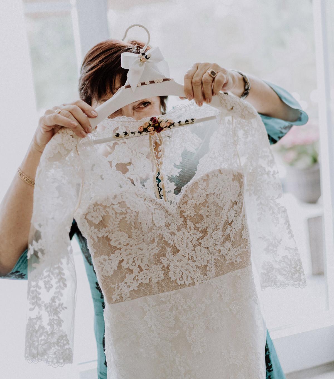 Hochzeitsfoto Brautkleid Spitze mit langen Ärmeln und schöner Kleiderbügel Hochzeit - Gut Schloss Golm Potsdam Hochzeitsfotograf © www.hochzeitslicht.de