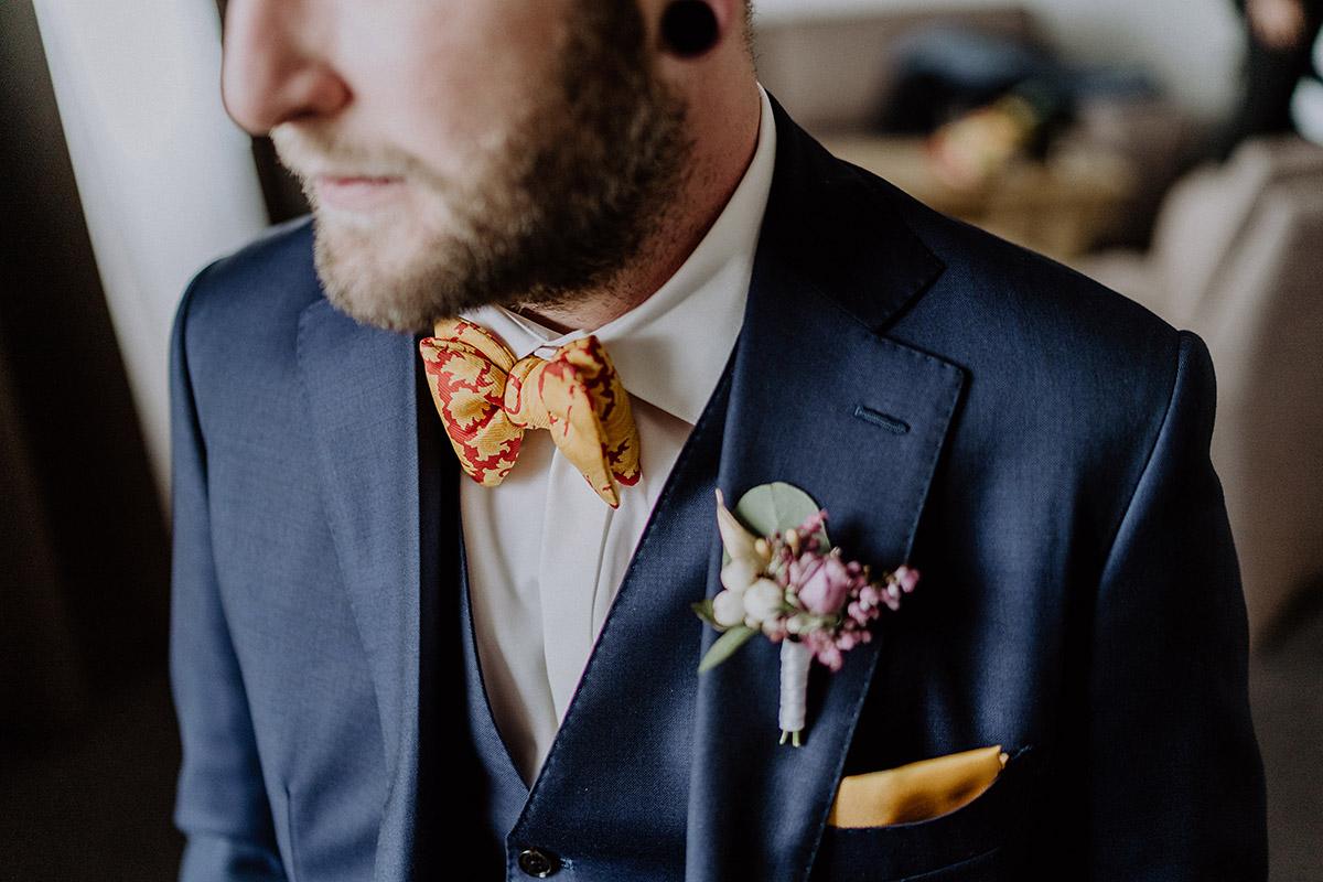 Bräutigam in dunkelblauem Anzug mit roter und gelber Fliege und Ansteckstrauß von Kopflegenden - Gut Schloss Golm Potsdam Hochzeitsfotograf © www.hochzeitslicht.de