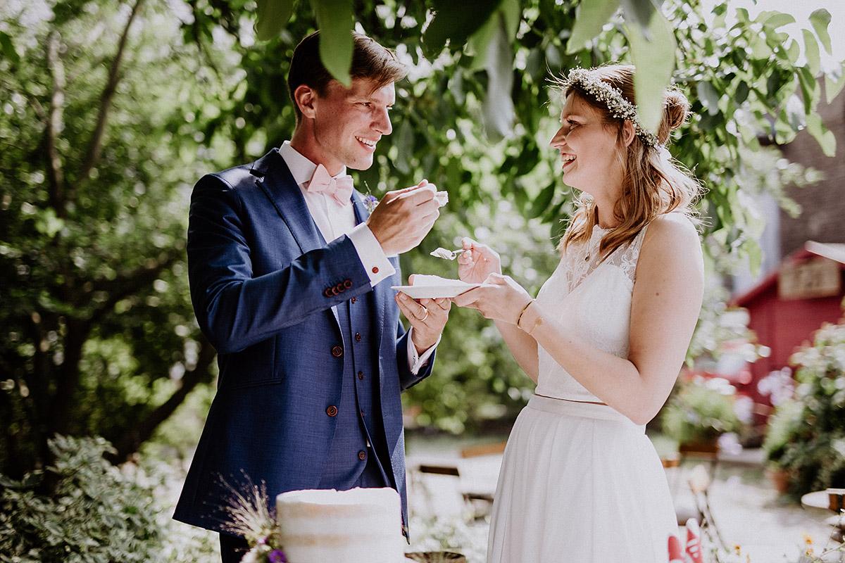 Brautpaar beim Anschneiden dreistöckige Hochzeitstorte Naked Cake mit Blumen - Vierseithofcafé Brandenburg Hochzeitsfotograf © www.hochzeitslicht.de