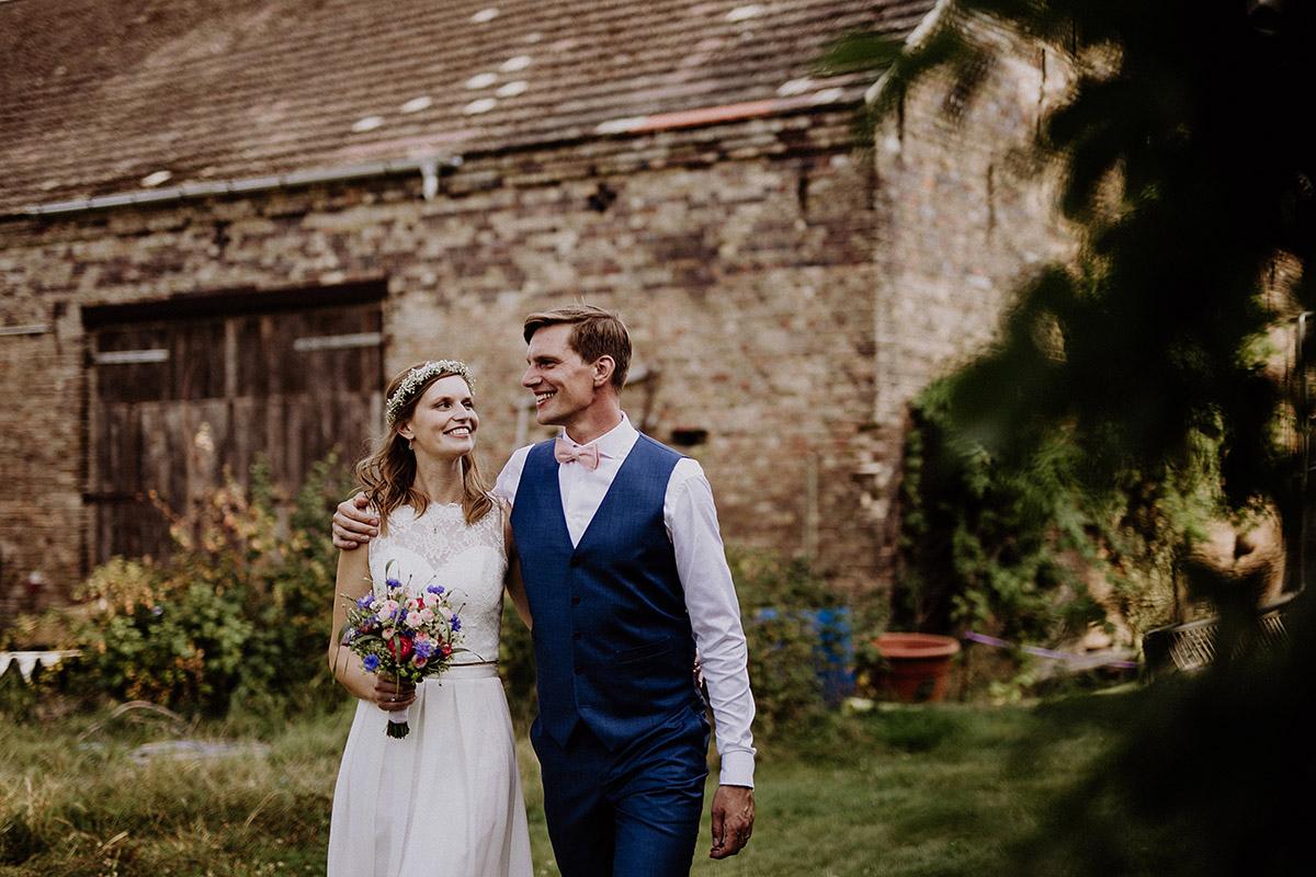 Hochzeitsfoto Brautpaar mit Bräutigam in blauem Anzug und Braut in Zweiteiler Brautkleid - Vierseithofcafé Brandenburg Hochzeitsfotograf © www.hochzeitslicht.de