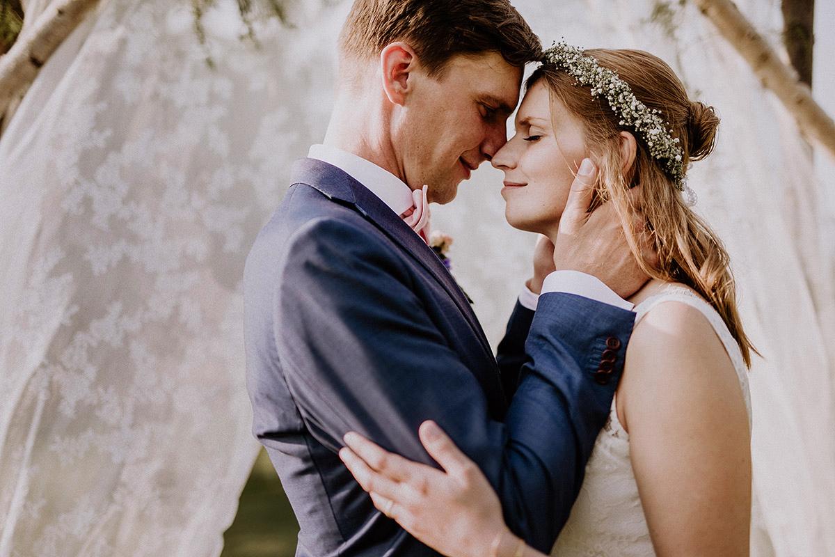 Brautpaarfoto vor Traubogen aus Spitze und Holz - Vierseithofcafé Brandenburg Hochzeitsfotograf © www.hochzeitslicht.de