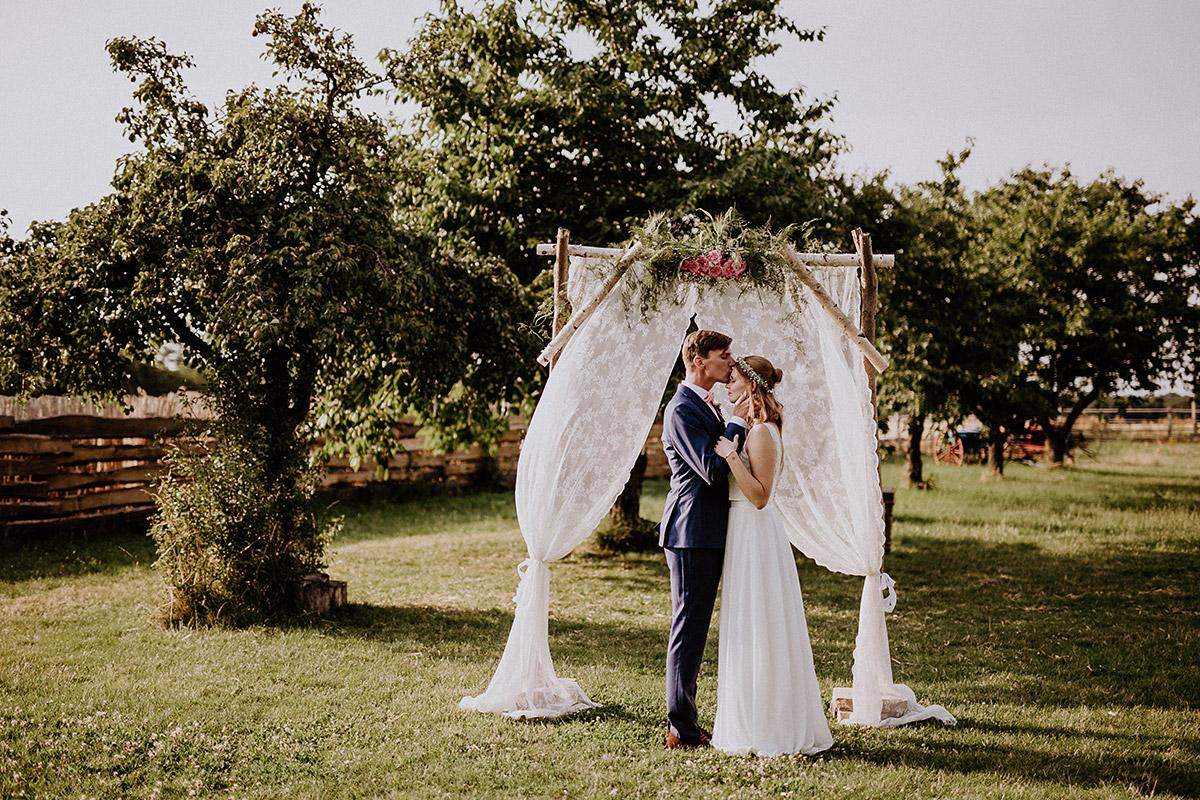 Hochzeitsfoto Brautpaar vor Traubogen aus Spitze und Holz bei Boho-Hochzeit - Vierseithofcafé Brandenburg Hochzeitsfotograf © www.hochzeitslicht.de