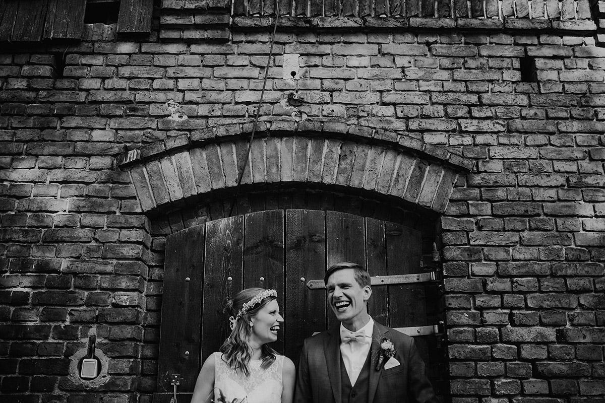 fröhliches Brautpaarfoto bei entspannter Landhochzeit - Vierseithofcafé Brandenburg Hochzeitsfotograf © www.hochzeitslicht.de