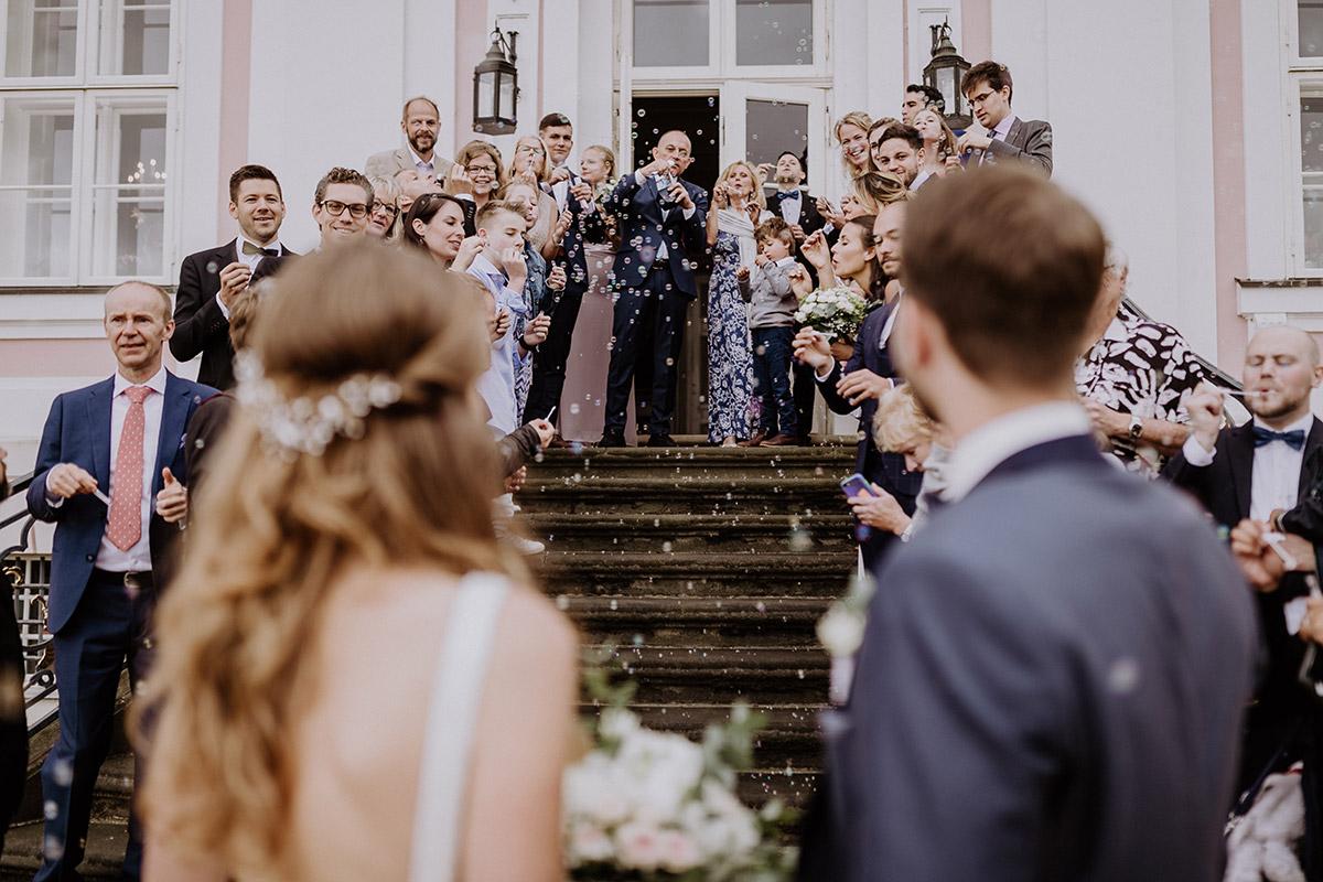 Gäste feiern Brautpaar mit Seifenblasen Hochzeit - Schloss Friedrichsfelde Hochzeitsfotograf © www.hochzeitslicht.de