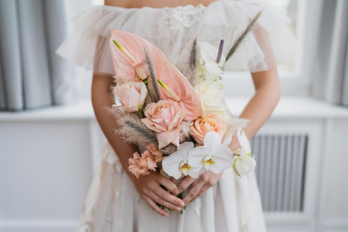 moderner asymmetrischer Brautstrauß Berlin mit Orchideen und Papageienblume in Pastelltönen Apricot und Koralle - Moderne Hochzeitsfotografie Berlin © www.hochzeitslicht.de