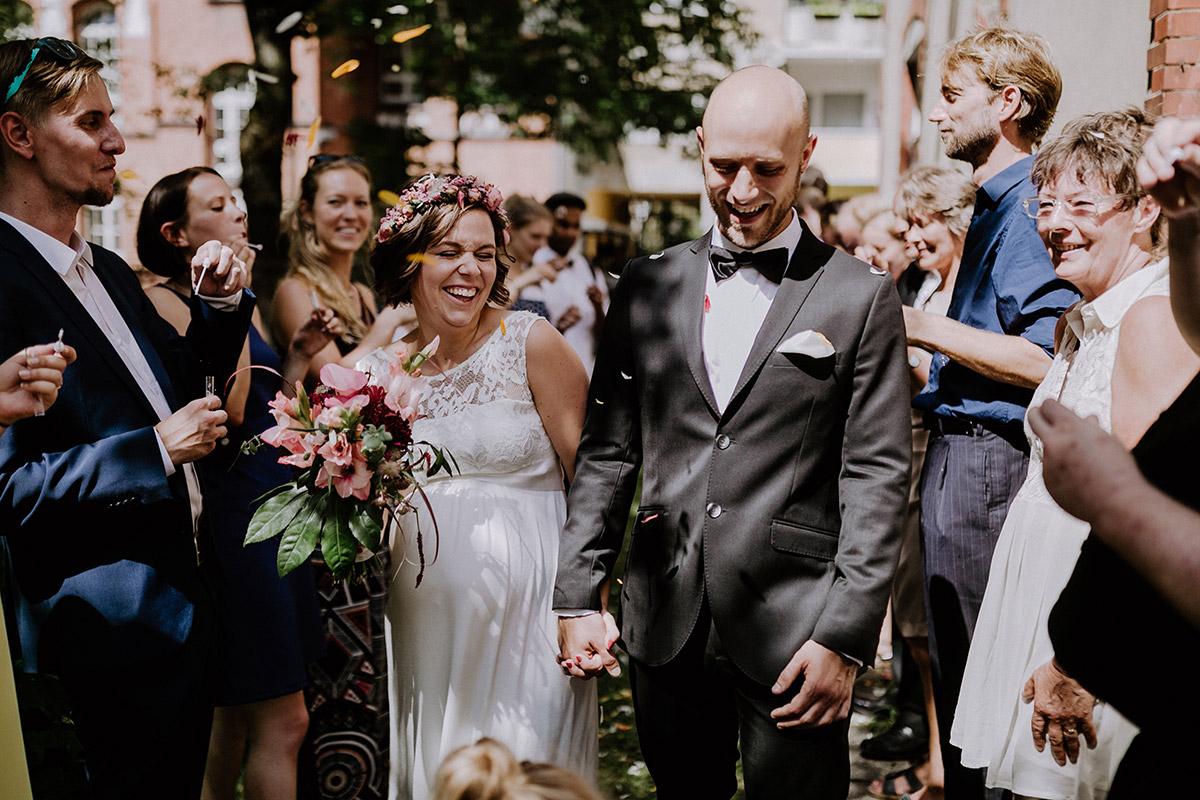 Hochzeitsreportagefoto Auszug Braut und Bräutigam aus Standesamt mit Gästen im Spalier mit Seifenblasen - Hochzeitsfotograf Standesamt Rathaus Schöneberg © www.hochzeitslicht.de