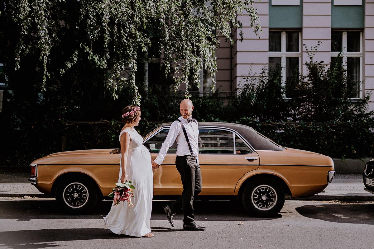 Hochzeitsfoto bei Standesamt Hochzeit von Bräutigam und schwangerer Braut, bodenlanges weißes Brautkleid mit Spitzenoberteil für Hochzeit mit Babybauch - Hochzeitsfotograf Standesamt Rathaus Schöneberg © www.hochzeitslicht.de