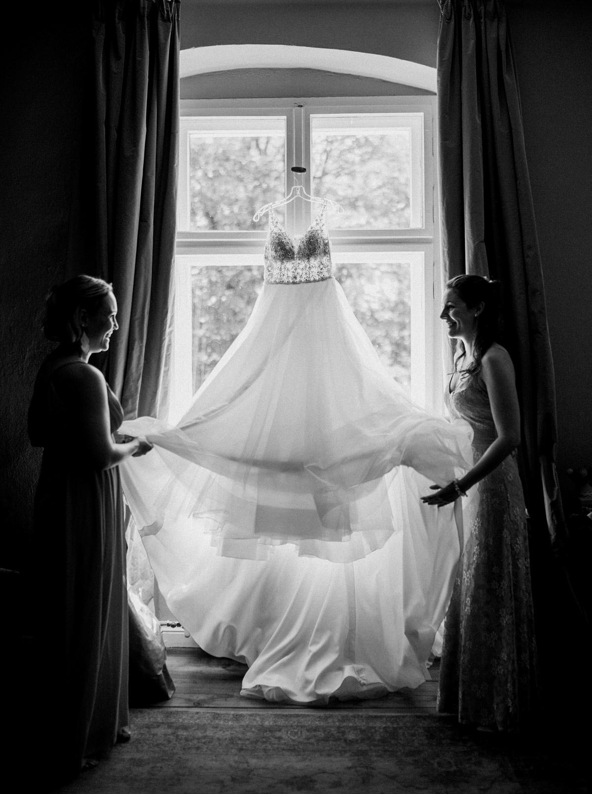 Idee Hochzeitsfoto Brautkleid Tüll Spitze lange Schleppe vor Fenster im Gegenlicht auf schönem Kleiderbügel - Schloss Blankensee Hochzeit Hochzeitsfotograf Berlin © www.hochzeitslicht.de