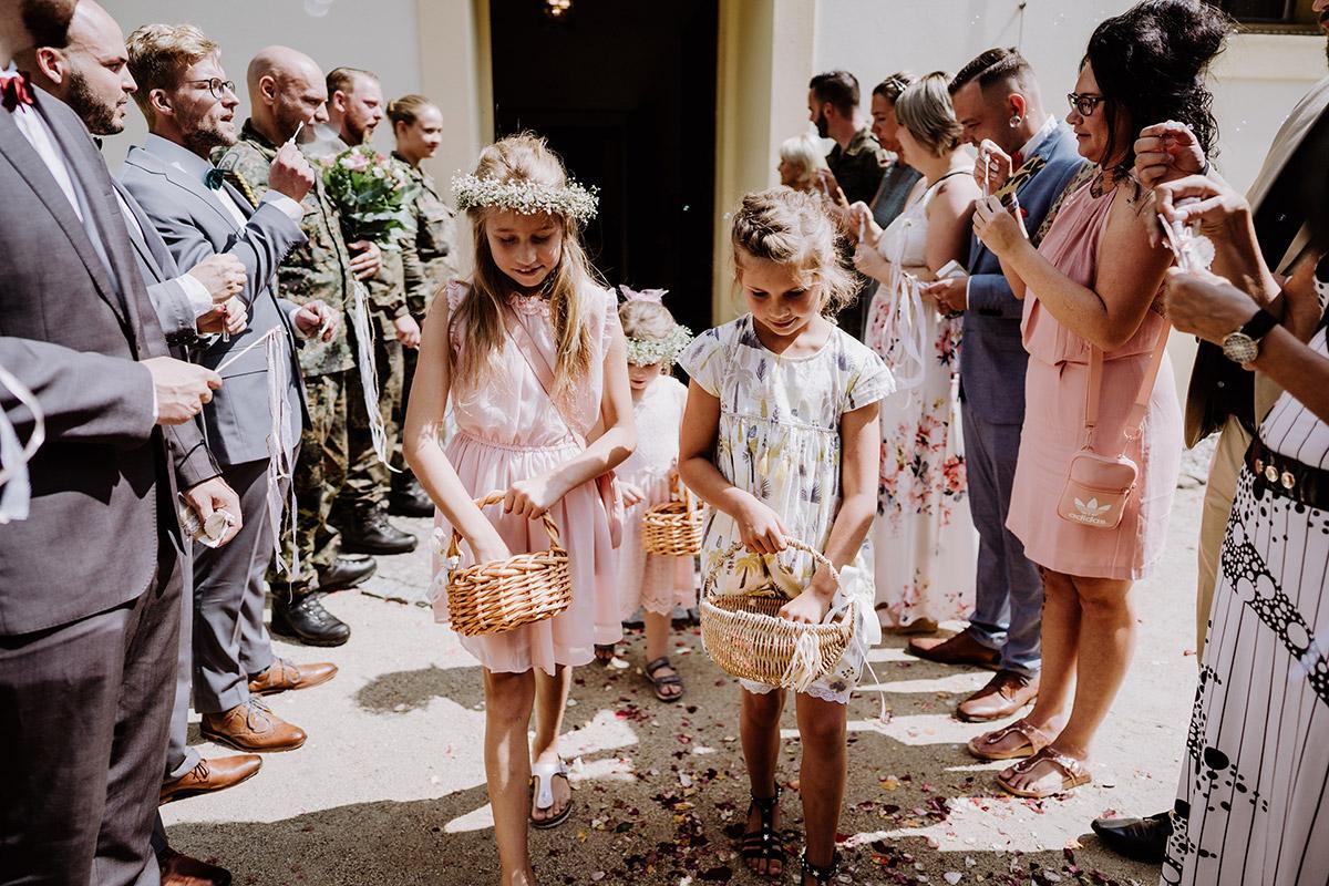 Hochzeitsfoto Auszug Brautpaar Schlosskirche Schöneiche Blumenmädchen - Hochzeit in Scheune und Standesamt in Kirche Berlin von Hochzeitsfotografin © www.hochzeitslicht.de