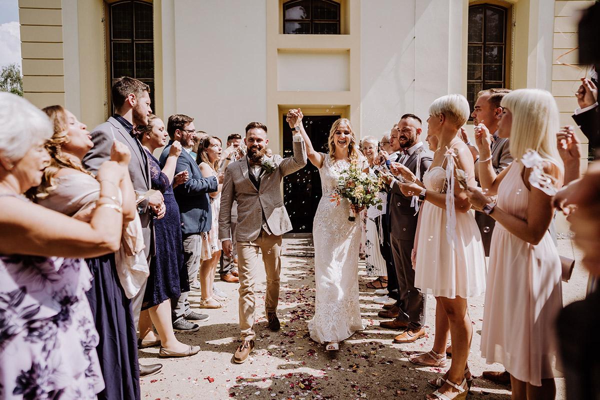 Hochzeitsfotografie Auszug Brautpaar Gäste Spalier Seifenblasen - Hochzeit in Scheune und Standesamt in Kirche Berlin von Hochzeitsfotografin © www.hochzeitslicht.de