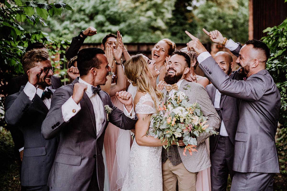 Idee lustiges Hochzeitsfoto Brautpaar mit Gästen - Hochzeit in Scheune und Standesamt in Kirche Berlin von Hochzeitsfotografin © www.hochzeitslicht.de