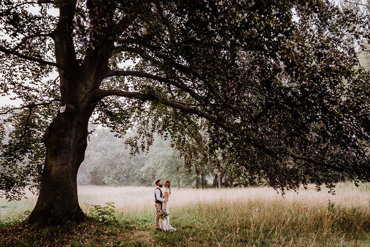 Inspiration Brautpaarfoto unter Baum in der Natur bei Landhochzeit - Hochzeit in Scheune und Standesamt in Kirche Berlin von Hochzeitsfotografin © www.hochzeitslicht.de