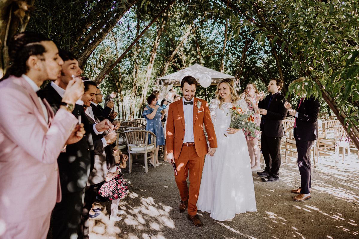 Hochzeitsfoto Auszug Brautpaar Standesamt unter freiem Himmel Gäste Spalier Seifenblasen - Standesamt Weidendom und Spreewood Distillers DIY-Herbst-Hochzeit von Spreewald Hochzeitsfotografin aus Berlin © www.hochzeitslicht