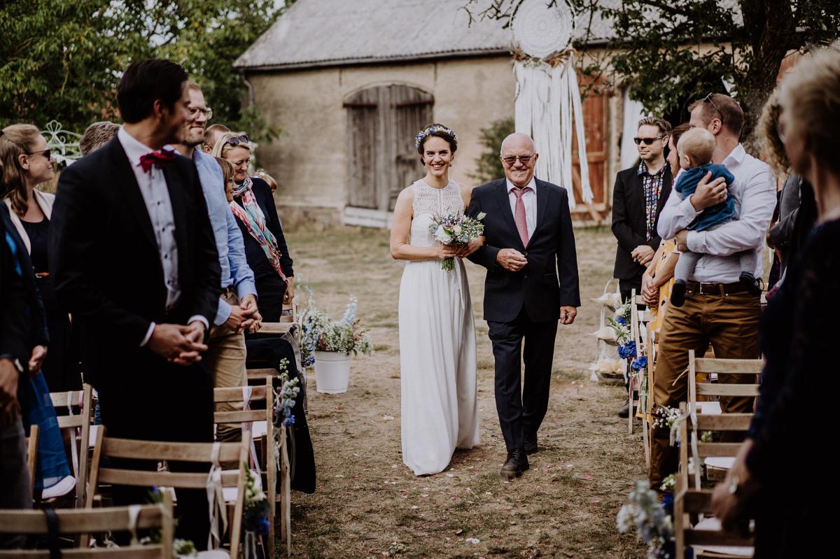 Hochzeitsfoto Einzug Braut freie Trauung draußen Gartenhochzeit - Boho-Scheunenhochzeit in Brandenburg im Schmetterlingsgarten mit Hochzeitsfotografin aus Berlin © www.hochzeitslicht.de