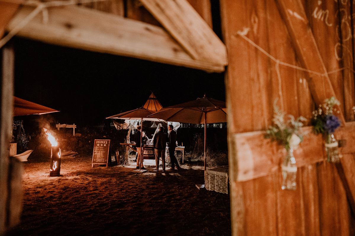 Idee Hochzeitsfeier outdoor Bar am Lagerfeuer - Boho-Scheunenhochzeit in Brandenburg im Schmetterlingsgarten mit Hochzeitsfotografin aus Berlin © www.hochzeitslicht.de