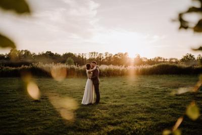 Hochzeitsfoto Brautpaar auf Feld bei Sonnenuntergang - Spreewald Hochzeitsfotografin im Standesamt Weidendom Hochzeit am Wasser im Spreewaldresort Seinerzeit © www.hochzeitslicht.de