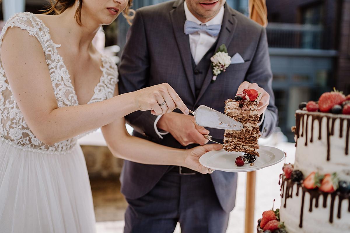 Hochzeitsreportagefoto Anschneiden Hochzeitstorte - Spreewald Hochzeitsfotografin im Standesamt Weidendom Hochzeit am Wasser im Spreewaldresort Seinerzeit © www.hochzeitslicht.de