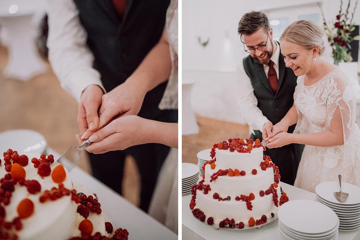 Hochzeitsfoto Anschneiden Hochzeitstorte dreistöckig weiß mit Beeren - vintage DIY Waldhochzeit in Berlin von Villa Schützenhof Hochzeitsfotografin © www.hochzeitslicht.de