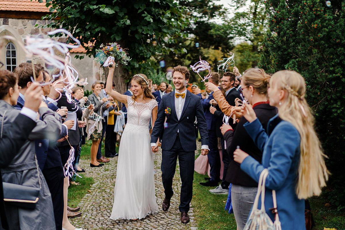 Hochzeitsfotografie Auszug Brautpaar aus Kirche Gäste Spalier Seifenblasen - Hochzeit am Wasser im Restaurantschiff Alte Liebe und Dorfkirche Gatow von Hochzeitsfotografin Berlin © www.hochzeitslicht.de