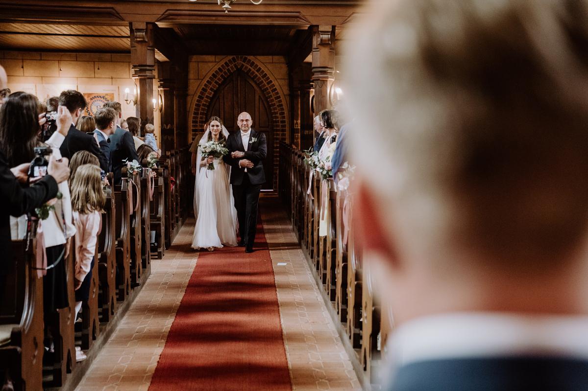 Hochzeitsfoto Einzug Braut mit Vater - Scheunenhochzeit in Brandenburg im Gutshaus Penzlin Hochzeitsfotograf Berlin © www.hochzeitslicht.de