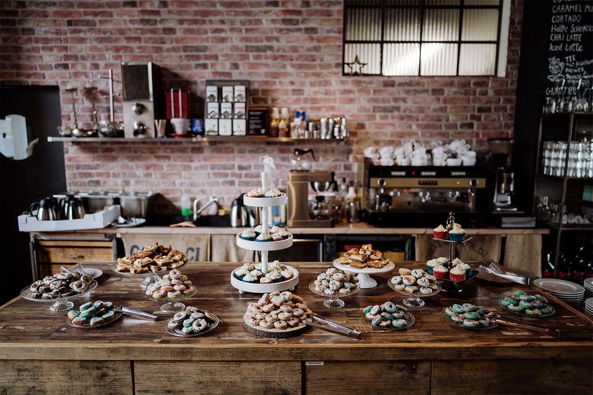 Hochzeitsfoto modern Kuchenbuffet Donuts Cupcakes - urbane Hochzeitsfotos im Restaurant Sonnendeck Hochzeitslocation am Wasser Hochzeitsfotograf Berlin © www.hochzeitslicht.de