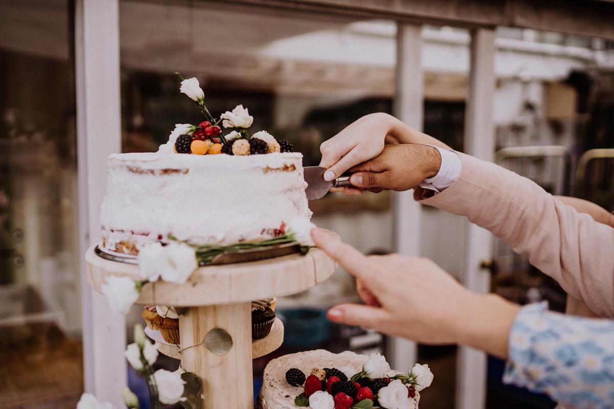 Hochzeitsbild Brautpaar schneidet Hochzeitstorte an - Persische Boho-Chic Hochzeit in der Malzfabrik Berlin von Hochzeitsfotografin aus Berlin Friedrichshain © www.hochzeitslicht.de #hochzeitslicht