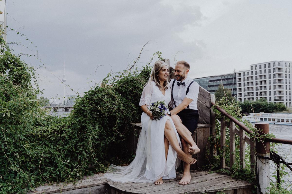 Fotoshooting Brautpaar Sommerhochzeit barfuß kurze Hosen Bräutigam - Hochzeitsfotograf in Hochzeitslocation mit Strand an der Spree im Sage Restaurant Berlin © www.hochzeitslicht.de #hochzeitslicht