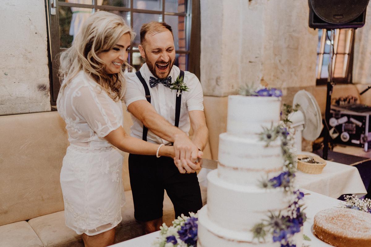 Hochzeitsfoto Brautpaar schneidet Hochzeitstorte an - Hochzeitsfotograf in Hochzeitslocation mit Strand an der Spree im Sage Restaurant Berlin © www.hochzeitslicht.de #hochzeitslicht