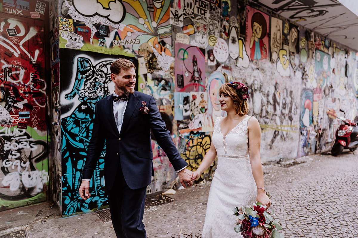 natürliche Hochzeitsfotografie Braut und Bräutigam im Gehen halten Hände - Hochzeit Berlin Friedrichshain in Hochzeitslocation Old Smithy's Dizzle von Boho Hochzeitsfotograf © www.hochzeitslicht.de #hochzeitslicht
