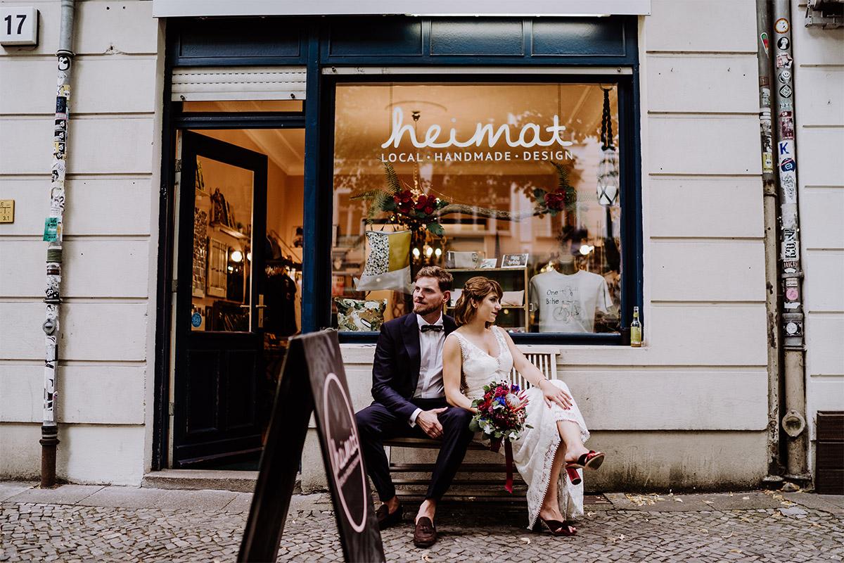 Paarfotoshooting in der Stadt Idee Brautpaar sitzt vor Laden - Hochzeit Berlin Friedrichshain in Hochzeitslocation Old Smithy's Dizzle von Boho Hochzeitsfotograf © www.hochzeitslicht.de #hochzeitslicht