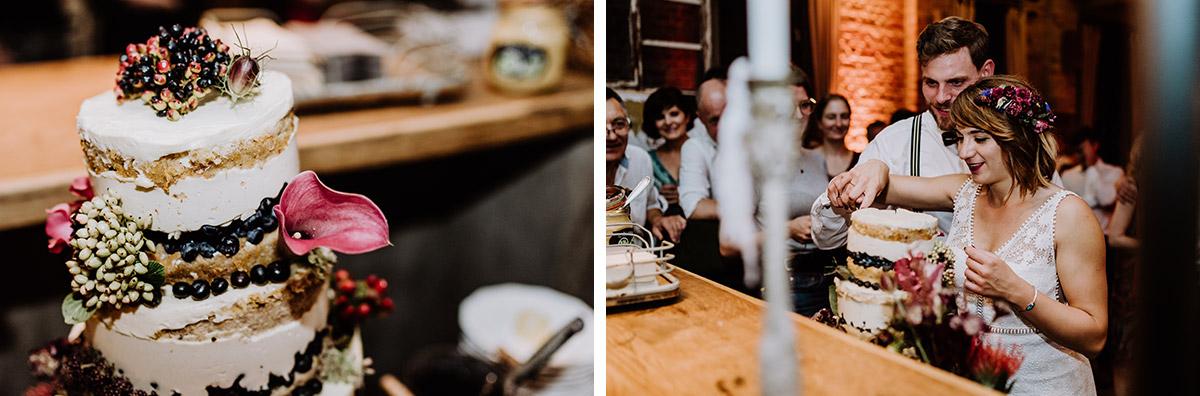 Hochzeitsfotografien Anschneiden Hochzeitstorte - Hochzeit Berlin Friedrichshain in Hochzeitslocation Old Smithy's Dizzle von Boho Hochzeitsfotograf © www.hochzeitslicht.de #hochzeitslicht