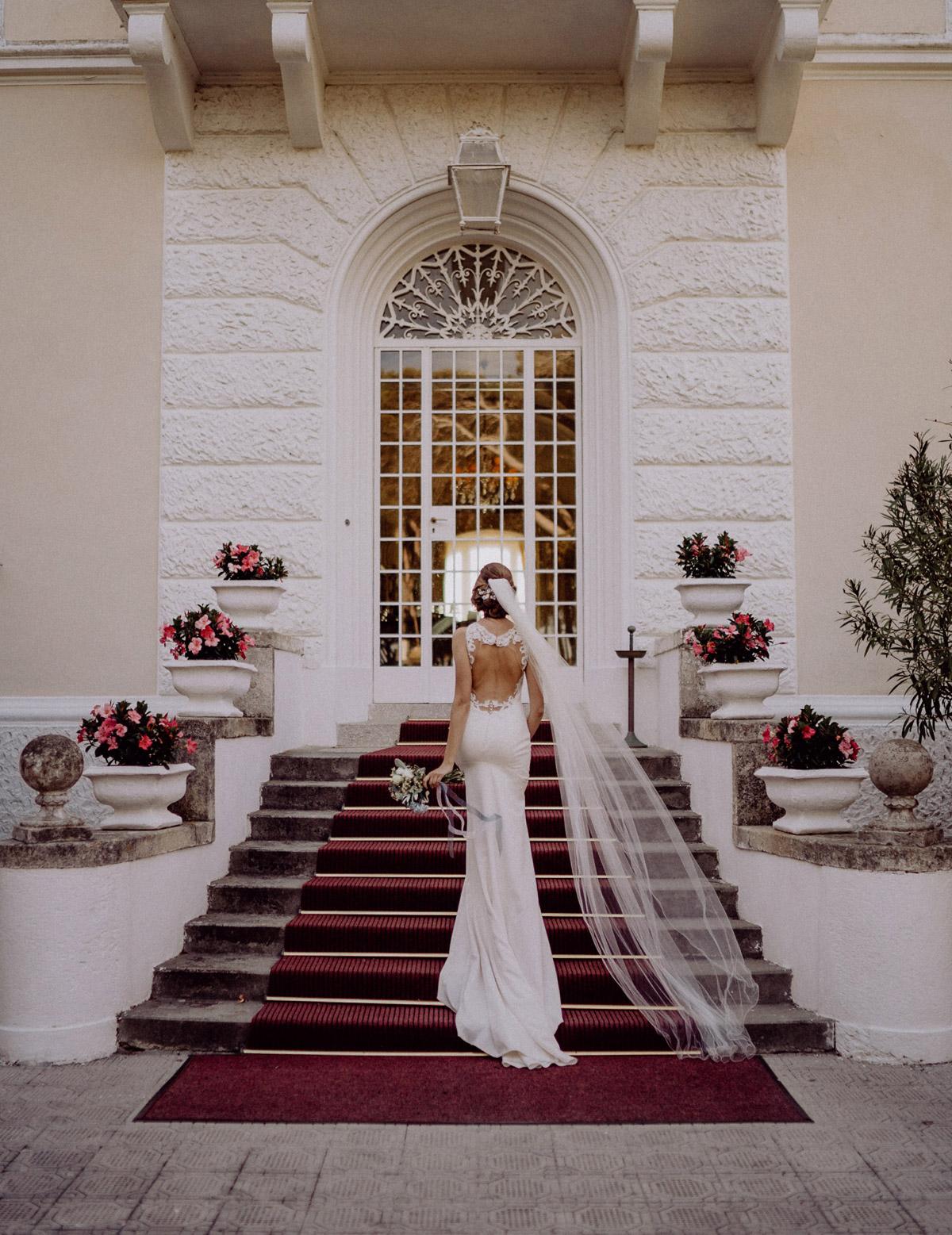 Hochzeitsfotos Hochzeitsbilder Ideen Braut von hinten vor Standesamt ausgefallen in rückenfreiem Kleid auf Treppe mit langem Schleier und Hochsteckfrisur auf maritimer Hochzeit #hochzeitslicht Toskana Hochzeitsfotos und Hochzeitsfilm © Destination-Hochzeitsfotograf www.hochzeitslicht.de