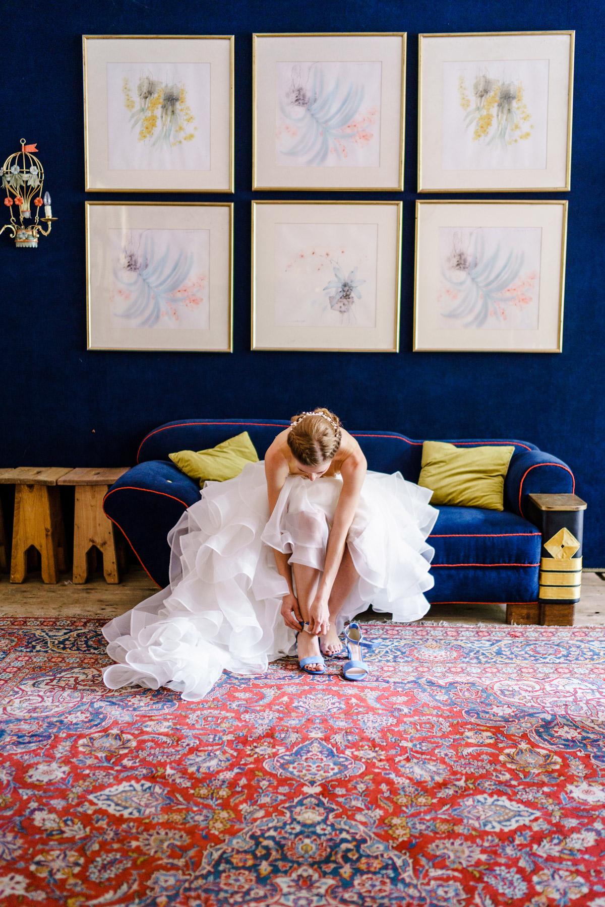 vintage Hochzeitsfoto Idee: Hochzeitsmoment Braut mit vintage Hochzeitskleid zieht beim Getting Ready blaue Brautschuhe an auf vintage Hochzeit in Berlin - so schön kann Heiraten mit freier Trauung in der Hochzeitslocation Von Greifswald sein - Hochzeitsfotos von #hochzeitslicht © www.hochzeitslicht.de #brautkleid #standesamt #braut #hochzeitsbild