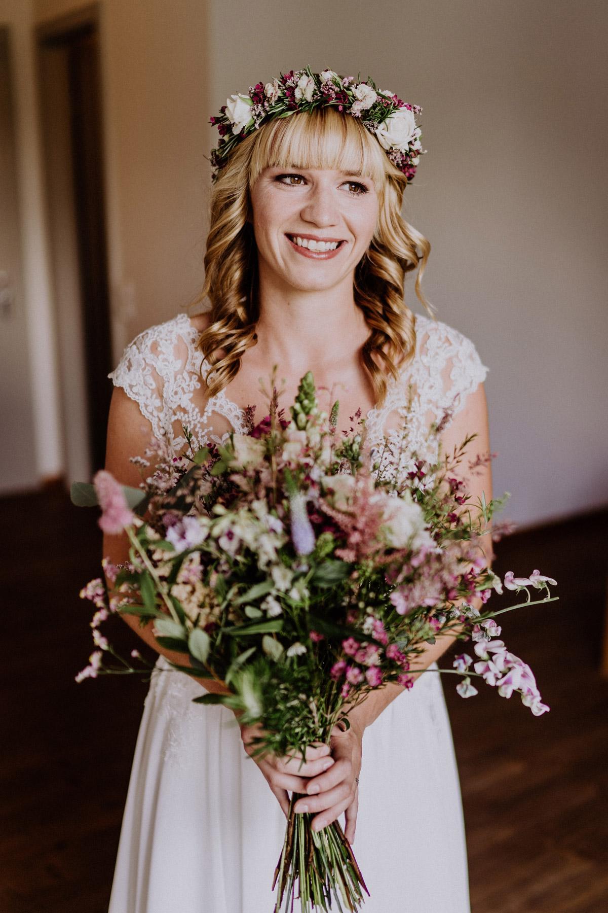 Braut Make up Hochzeit natürlich blonde Haare braune Augen helle Haut; Brautfrisur mit Pony schulterlangen Locken und Haarkranz mit weißen und pinkroten Hochzeitsblumen #braut #brautmakeup #brautfrisur #hochzeitsfrisur