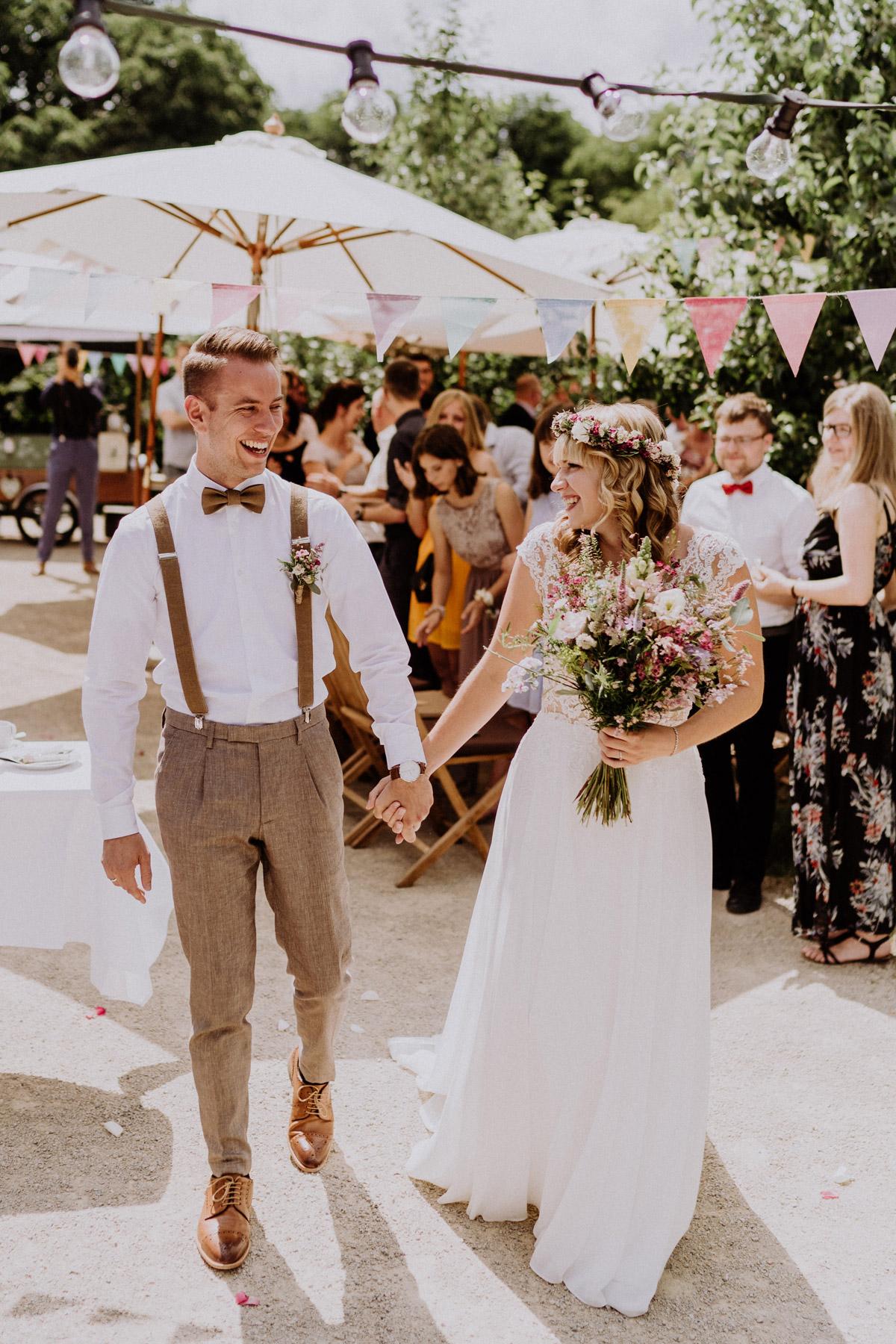Fotos Hochzeit Ideen Brautpaar Hand in Hand nach freier Trauung lacht sich glücklich an