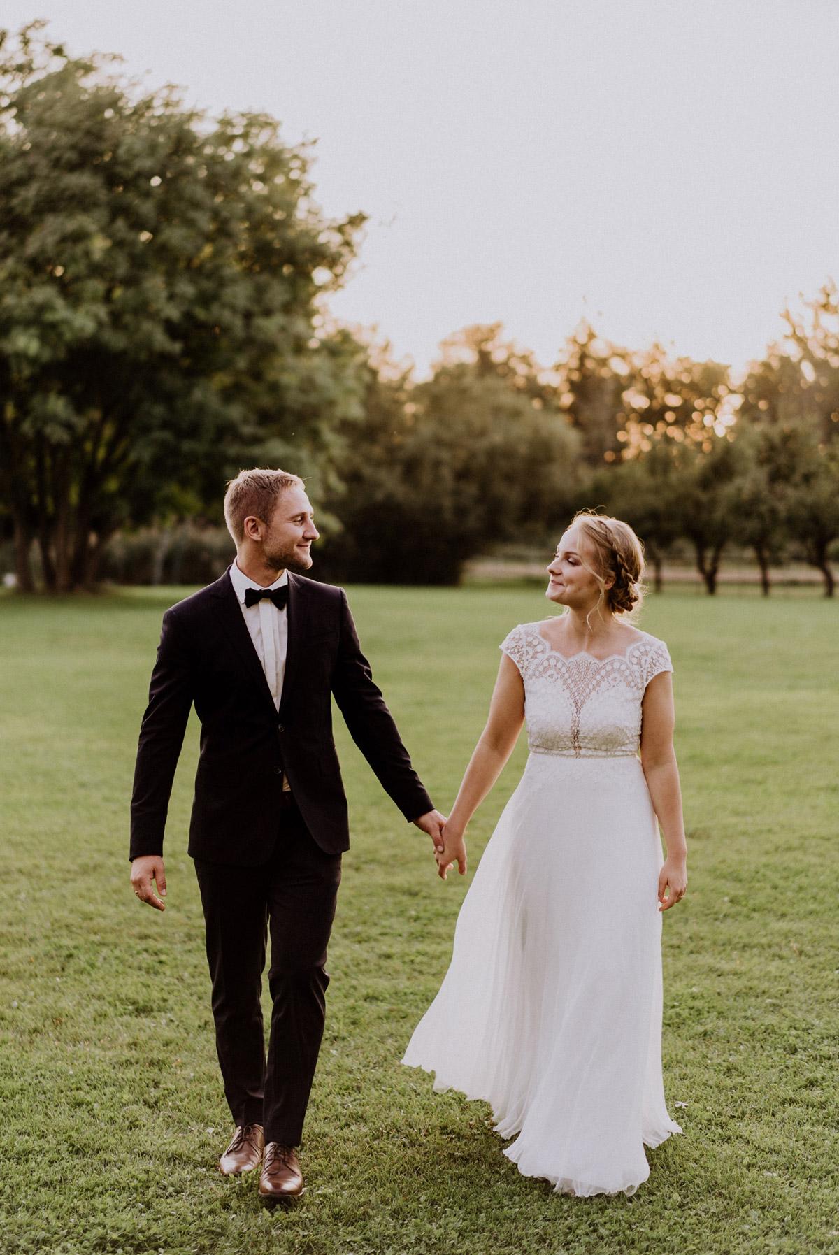 Hochzeit Paarfotos in Natur zum Sonnenuntergang auf Wiese Hochzeitspaar läuft Hand in Hand und schaut sich an