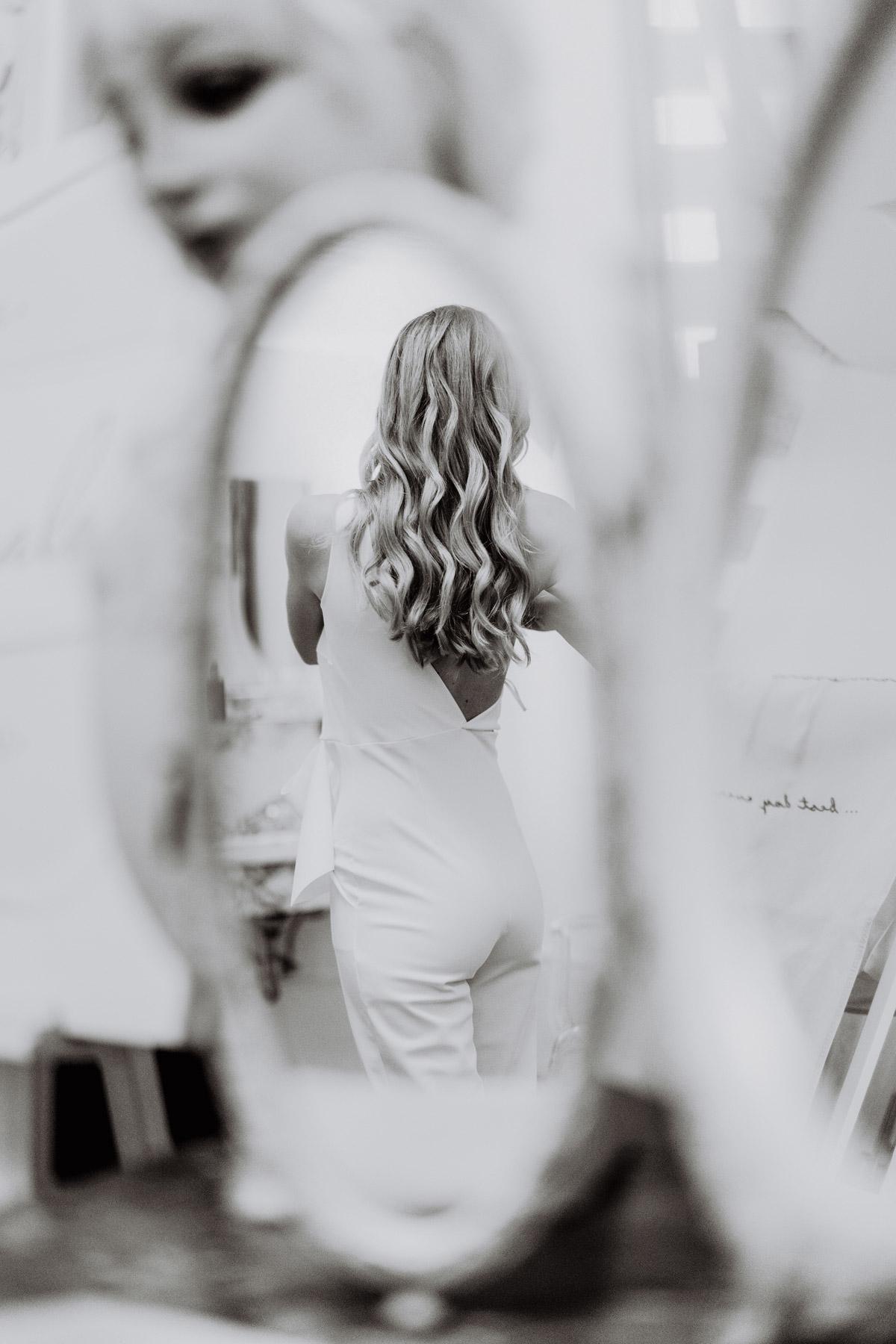 Standesamt Outfit Jumpsuit standesamtliche Hochzeit, Hochzeitsfrisur Braut mittellange Haare offen mit Locken, Braut beim Ankleiden Hochzeitsfoto Idee von Hochzeitsfotografin Berlin © www.hochzeitslicht.de #hochzeitslicht #brautfrisur #brautoutfit